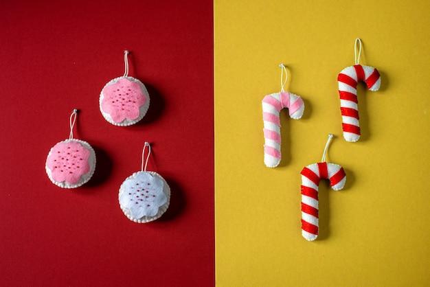 Kerst minimalistische rode en gele bakgrond met handgemaakte kerstversieringen: zuurstokken en kerstballen