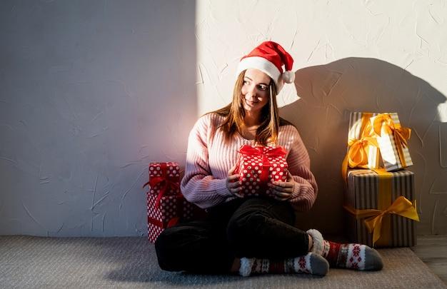 Kerst mis en nieuwjaar jonge vrouw in kerstmuts, omringd door cadeautjes
