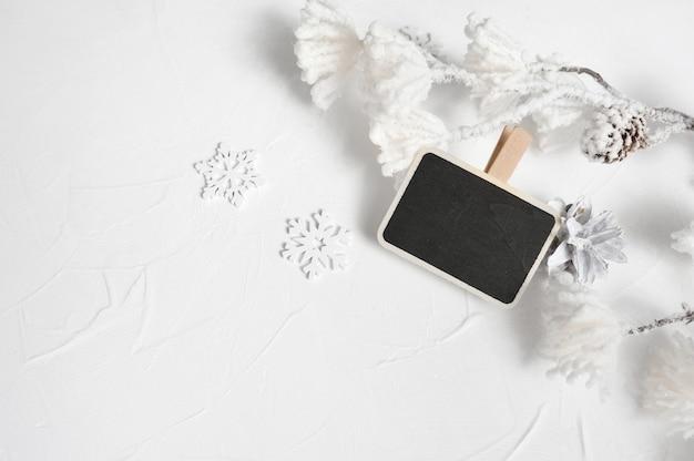 Kerst mock up compositie met plaats voor tekst. kerstmissneeuwvlokken, dennenappels en decorbloemen.
