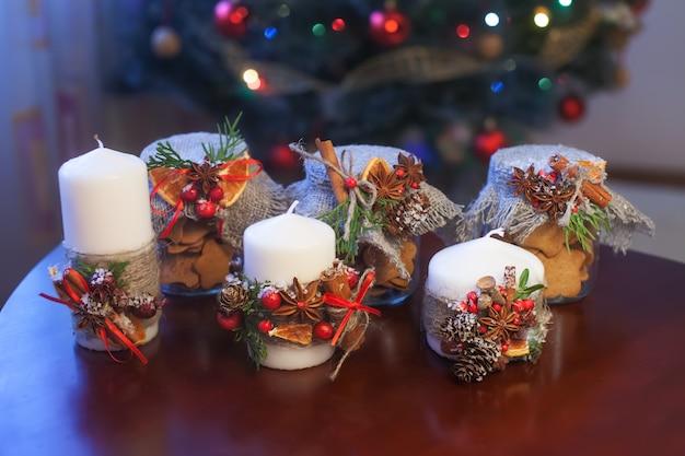 Kerst ñ ookies in een pot en decoratieve kaarsen op bruine tafel. kerst hulst. feestelijk decor