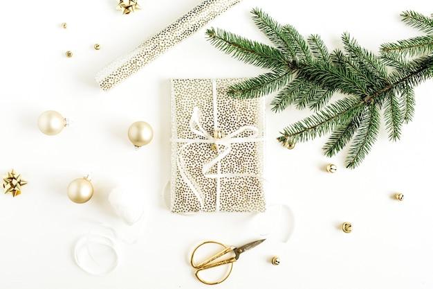 Kerst, nieuwjaar geschenkverpakkingen. vakantiesamenstelling met gouden decoraties en dennentakken op wit oppervlak. plat lag, bovenaanzicht