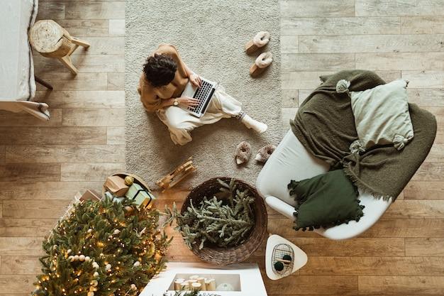 Kerst / nieuwjaar versierde huis woonkamer. mooie vrouw die op laptop werkt. versierde kerstboom, houten vloer, kussens. gezellig comfortabel interieur. thuiswerken. uitzicht van boven.