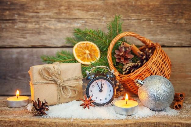 Kerst-nieuwjaarsamenstelling winter objecten wekker op houten achtergrond