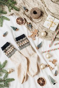 Kerst-nieuwjaarssamenstelling met wollen sokken, geschenkdoos, dennentakken, kerstballen, gemberkoekjes, stoksnoepjes, gebreide plaid