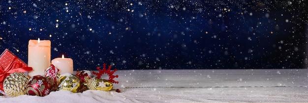 Kerst- of nieuwjaarsbanner samenstelling van balkaarsen en ornamenten met heldere bokeh en sneeuw