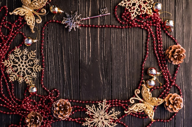 Kerst- of nieuwjaarsframe. kersttakken, dennenappels en rode ketting op houten planken