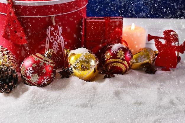 Kerst- of nieuwjaarssamenstelling van balkaarsen en ornamenten met heldere bokeh en sneeuw