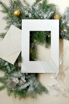 Kerst- of nieuwjaarswenskaart met sparrentakken met gouden kerstbal, champagneglazen, witboekframe, postenvelop. gouden bokehlicht. beige achtergrond. plat leggen, ruimte kopiëren