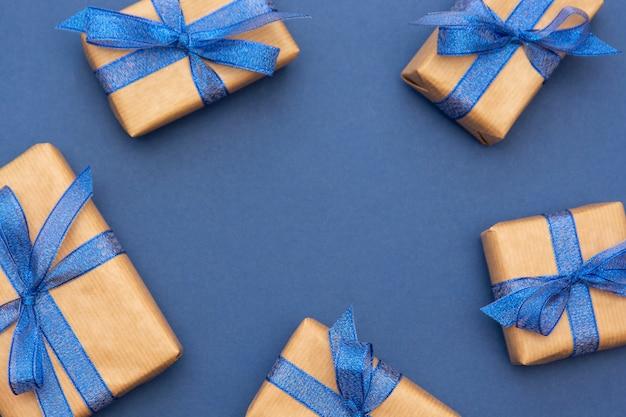 Kerst of verjaardag presenteert frame of rand, ambachtelijke papier gewikkeld geschenkdozen op blauw, plat lag.