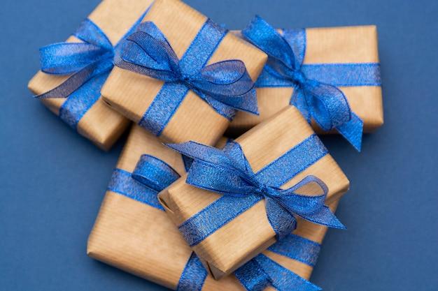 Kerst- of verjaardagscadeautjes, ambachtelijk verpakte geschenkdozen op blauw, plat liggend.