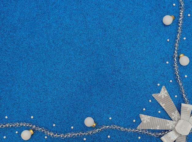 Kerst- of winterblauw met witte ballen, kralen, zilver klatergoud en strik met sneeuwvlokken.