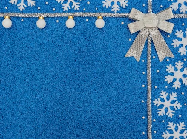 Kerst- of winterblauw met witte sneeuwvlokken, ballen, kralen, zilveren klatergoud en strik.
