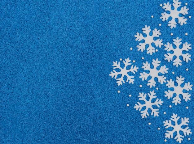 Kerst- of winterblauw met witte sneeuwvlokken en kralen