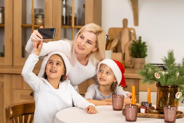 Kerst online familie gefeliciteerd. glimlachende europese blonde moeder en dochter met behulp van mobiele tablet voor video-oproep vrienden en ouders.