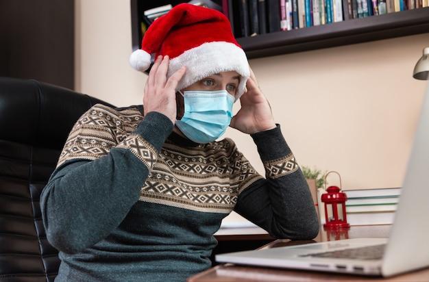 Kerst online felicitatie. geschokt en verrast jonge man in kerstman hoed en gezichtsmasker gesprekken met behulp van laptop voor video-oproep vrienden en kinderen. kerst tijdens coronavirus.