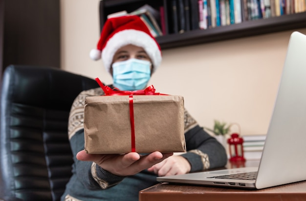 Kerst online felicitatie. jonge man in kerstman hoed en gezichtsmasker geeft een cadeau en praat met behulp van laptop voor video-oproep vrienden en kinderen. kerst tijdens coronavirus.