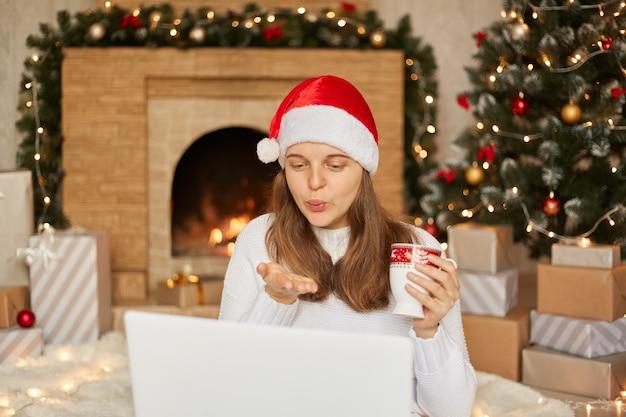Kerst online felicitatie, meisje in kerstman hoed en witte trui praat met iemand die laptop gebruikt voor videogesprek, luchtkus verzendt, beker met thee houdt, kamer feestelijk versierd.