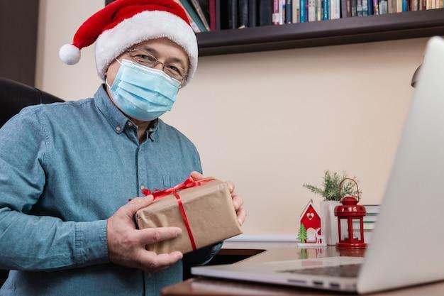 Kerst online felicitatie. senior man in kerstman hoed en gezichtsmasker geeft een geschenk en praat met behulp van laptop voor video-oproep vrienden en kinderen. kerst tijdens coronavirus.