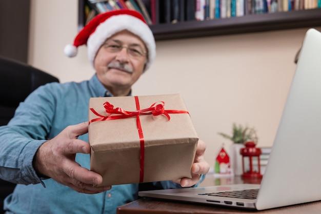 Kerst online felicitatie. senior man in kerstman hoed geeft een cadeau en praat met laptop voor video-oproep vrienden en kinderen. kerst tijdens coronavirus.