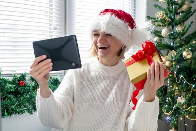 Kerst online gefeliciteerd. glimlachende vrouw met behulp van mobiele tablet voor video-oproep vrienden en ouders