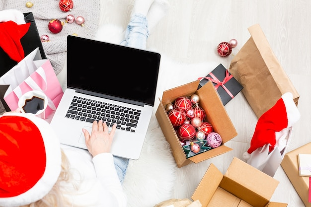 Kerst online winkelen bovenaanzicht. vrouwelijke koper met laptop, kopieer ruimte op het scherm. vrouw heeft koffie, koopt cadeautjes, bereidt zich voor op kerstavond, zit tussen geschenkdozen en pakketten. wintervakantie uitverkoop