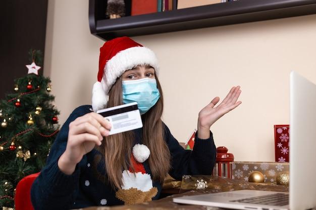Kerst online winkelen. een jong meisje in een hoed van de kerstman en een blauwe sweater in een medisch masker zit dichtbij laptop. de kamer is feestelijk versierd. kerst tijdens het coronavirus
