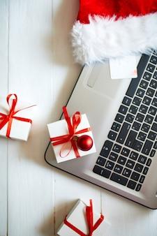 Kerst online winkelen, laptop, creditcard, kerstmuts en geschenkdoos op witte houten tafel, bovenaanzicht