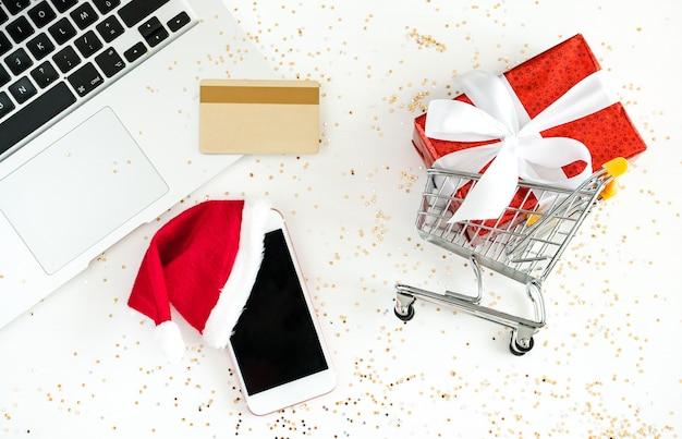 Kerst online winkelen. mini-winkelwagen, notebook, mobiel, creditcard en geschenkdoos
