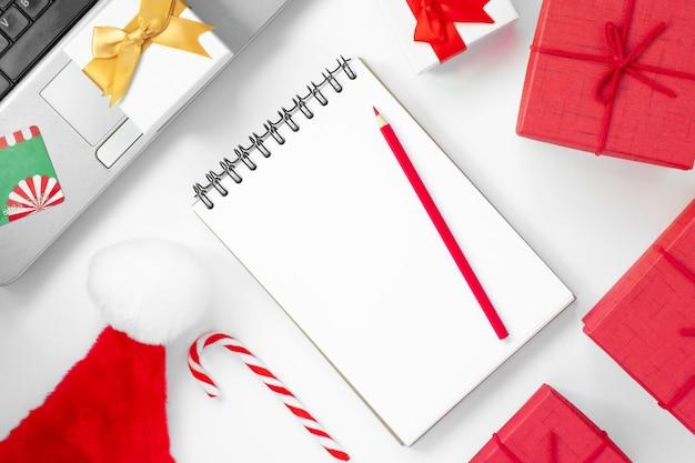 Kerst online winkelen plat lag notitieboekje met potlood boodschappenlijstje creditcard laptop
