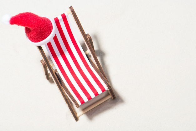 Kerst op het strand: een luie stoel met kerstmuts. bovenaanzicht