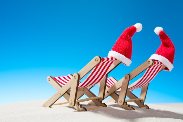 Kerst op het strand: twee stoelen en kerstmutsen