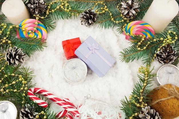 Kerst ornamenten, dennentakken en kleine geschenkdoos in de sneeuw