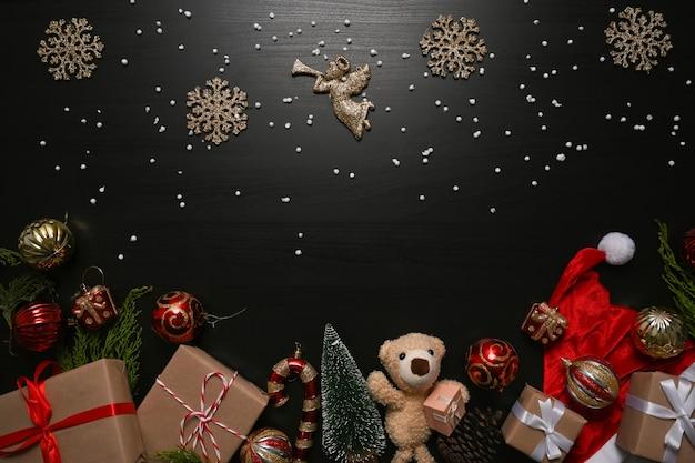 Kerst ornamenten, geschenkdozen en sparren takken op zwarte achtergrond.