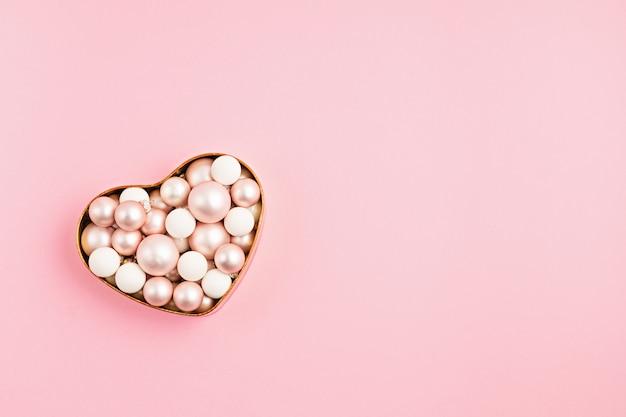 Kerst ornanemts in hartvormige doos op roze ondergrond