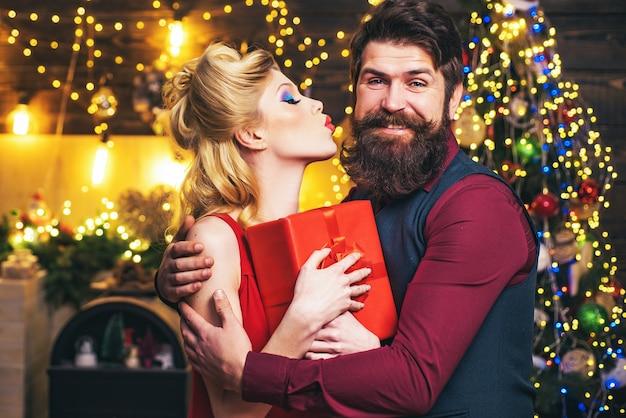 Kerst paar met geschenken - kus en omhelzing. oudejaarsavond vieren concept. prachtig nieuwjaar