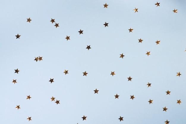 Kerst patroon gemaakt van gouden sterren op blauw