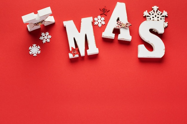 Kerst patroon gemaakt van houten kerst letters xmas, speelgoed, sneeuwvlokken en sterren op rood.