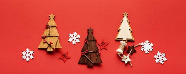 Kerst patroon gemaakt van houten kerst sparren speelgoed, sneeuwvlokken en sterren op rood. plat leggen. banner. bespotten.