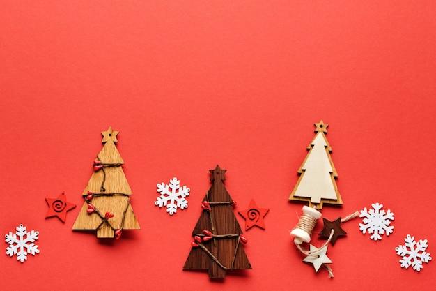 Kerst patroon gemaakt van houten kerst sparren speelgoed, sneeuwvlokken en sterren op rood.