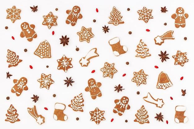 Kerst patroon gemaakt van peperkoek cookies en kruiden op witte ondergrond