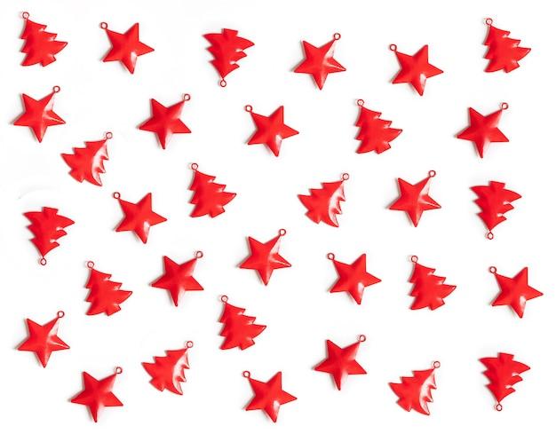 Kerst patroon met rode kerstversiering op witte achtergrond.