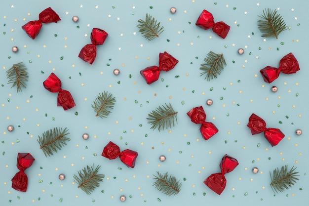 Kerst patroon van rode snoepjes, groene sparren en gouden confetti.