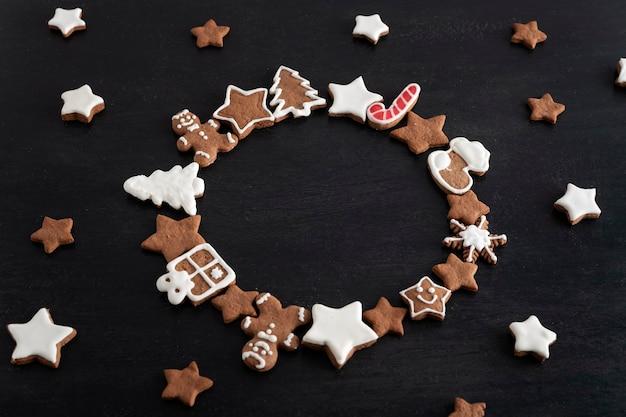 Kerst peperkoek in de vorm van een cirkel op zwarte achtergrond. geglazuurde beschilderde koekjes. kopieer ruimte.