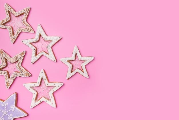 Kerst peperkoek sterren op zoete roze achtergrond. bovenaanzicht.