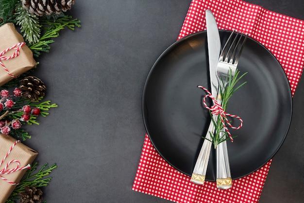 Kerst plaats instelling met zwarte plaat, vork en mes.