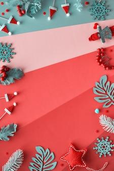 Kerst plat lag, frame van decoraties. winterbladeren, poppen, slinger en sneeuwvlokken. bovenaanzicht van veelkleurige geometrische gelaagd papier achtergrond