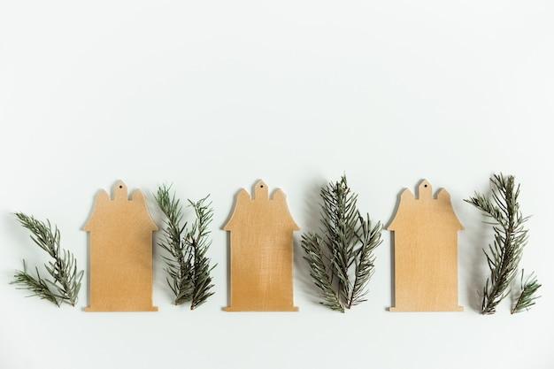 Kerst plat lag met dennentakken van dennen met houten huizen op de witte achtergrond