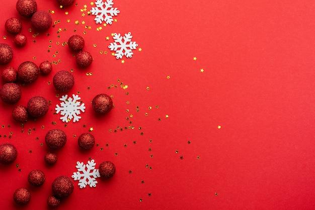 Kerst plat lag met fir tree, met kerstboom gemaakt van rood speelgoed ballen versierd gouden confetti in rode envelop op rood.