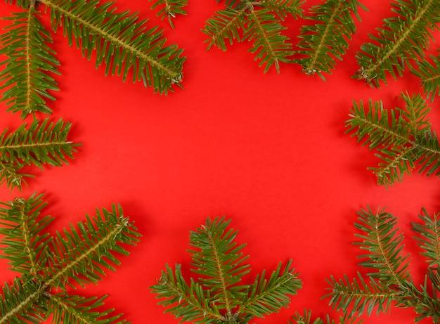 Kerst plat lag met fir tree takken frame op een rode achtergrond en kopieer ruimte binnen.