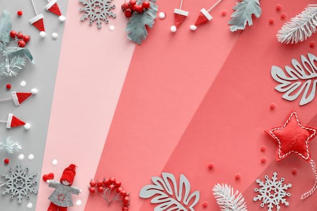 Kerst plat lag met frame van decoraties - winterbladeren, poppen, slinger en sneeuwvlokken. bovenaanzicht van veelkleurige geometrische gelaagde papier achtergrond in rood, oranje, roze, magenta en zilver.